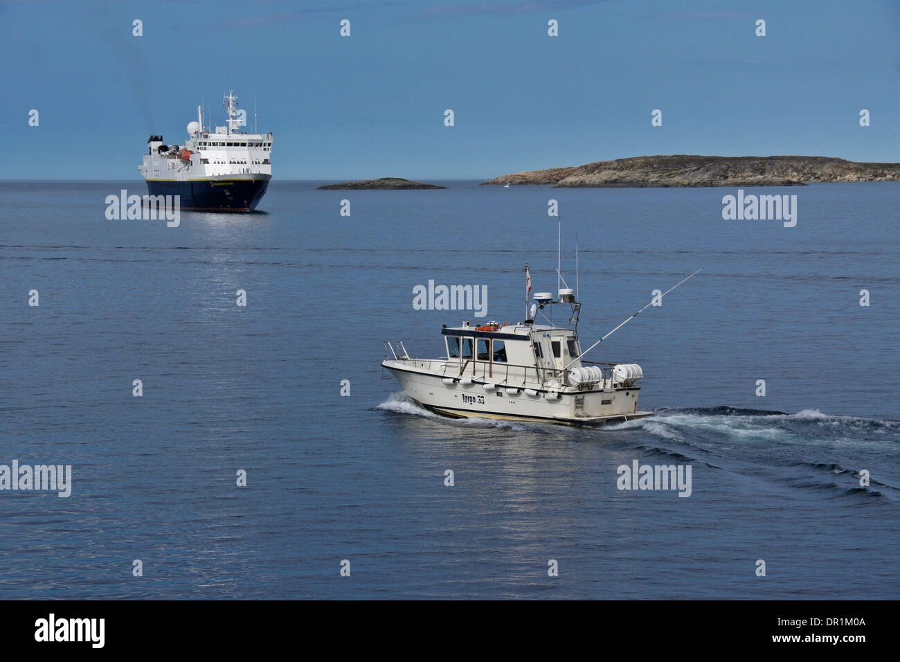 Fishing boat and National Geographic Explorer cruise ship in harbor, Sisimiut (Holsteinsborg), West Greenland - Stock Image