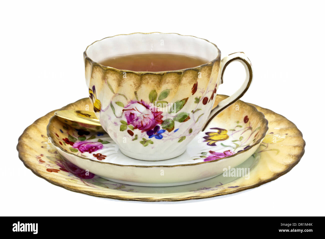 Tea in an antique china cup with saucer and dessert plate. - Stock Image