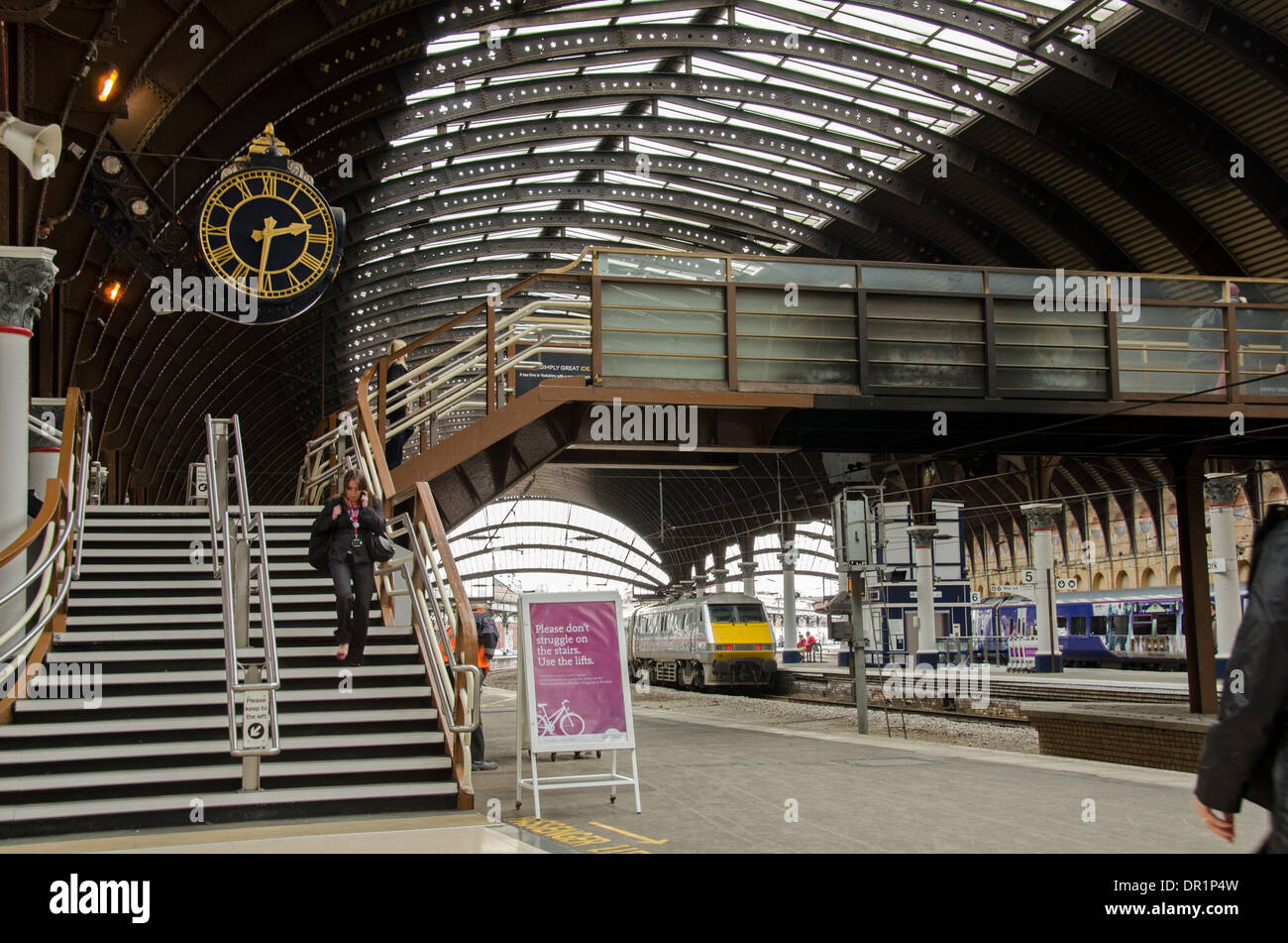 Interior of trainshed with iron & glass roof, stationary trains & woman walking by platform clock - York Railway Station, North Yorkshire, England, UK - Stock Image