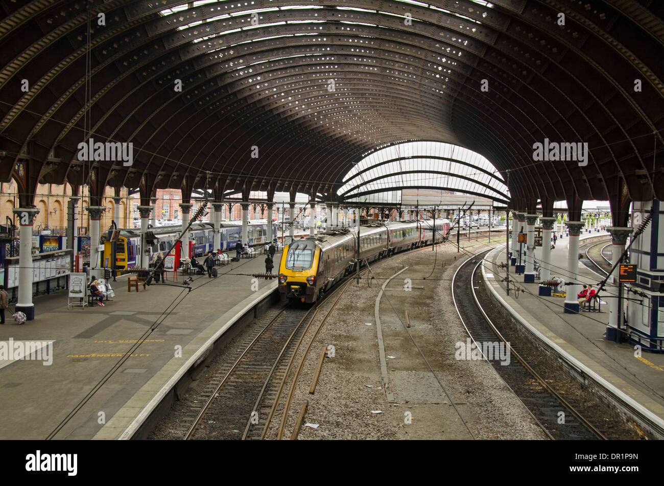 Interior view of trainshed with iron & glass roof, stationary trains & people waiting on platfom - York Railway Station, North Yorkshire, England, UK. - Stock Image