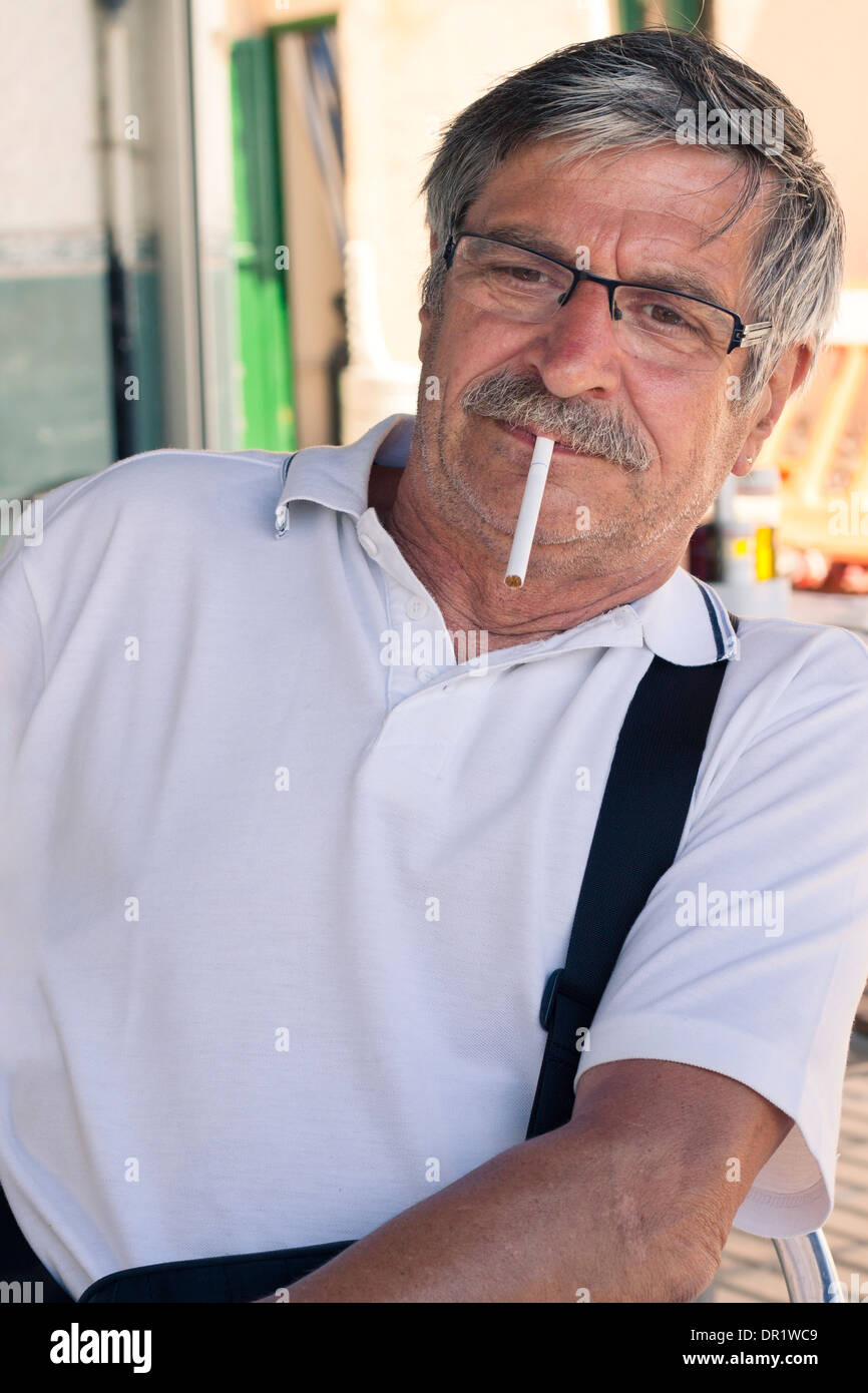 Photo of a senior smoker man with cigarette. - Stock Image