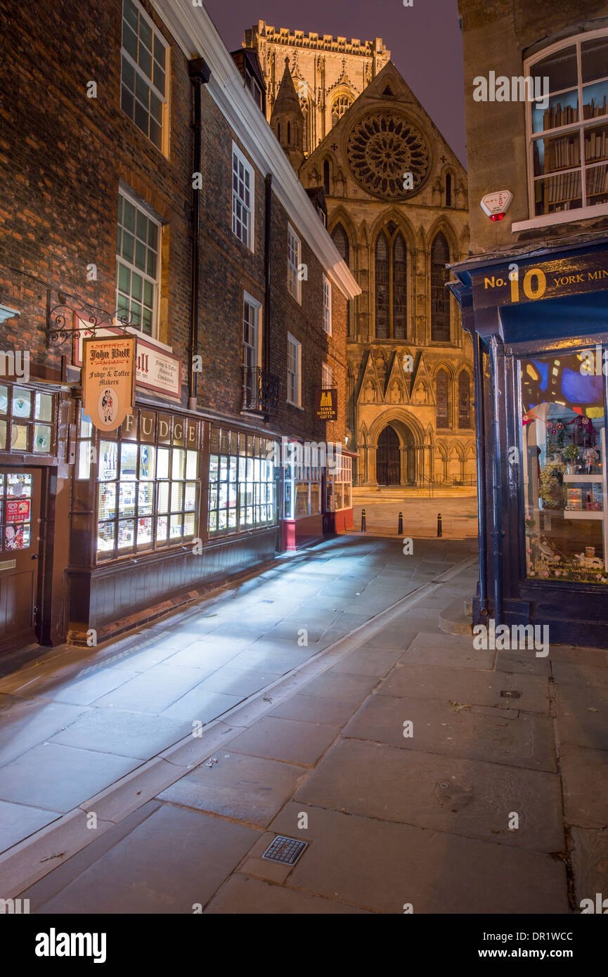 Evening view along Minster Gates to Minster's south entrance, a quaint, narrow lane lined with shops, some lit up - York North Yorkshire England, UK.r - Stock Image