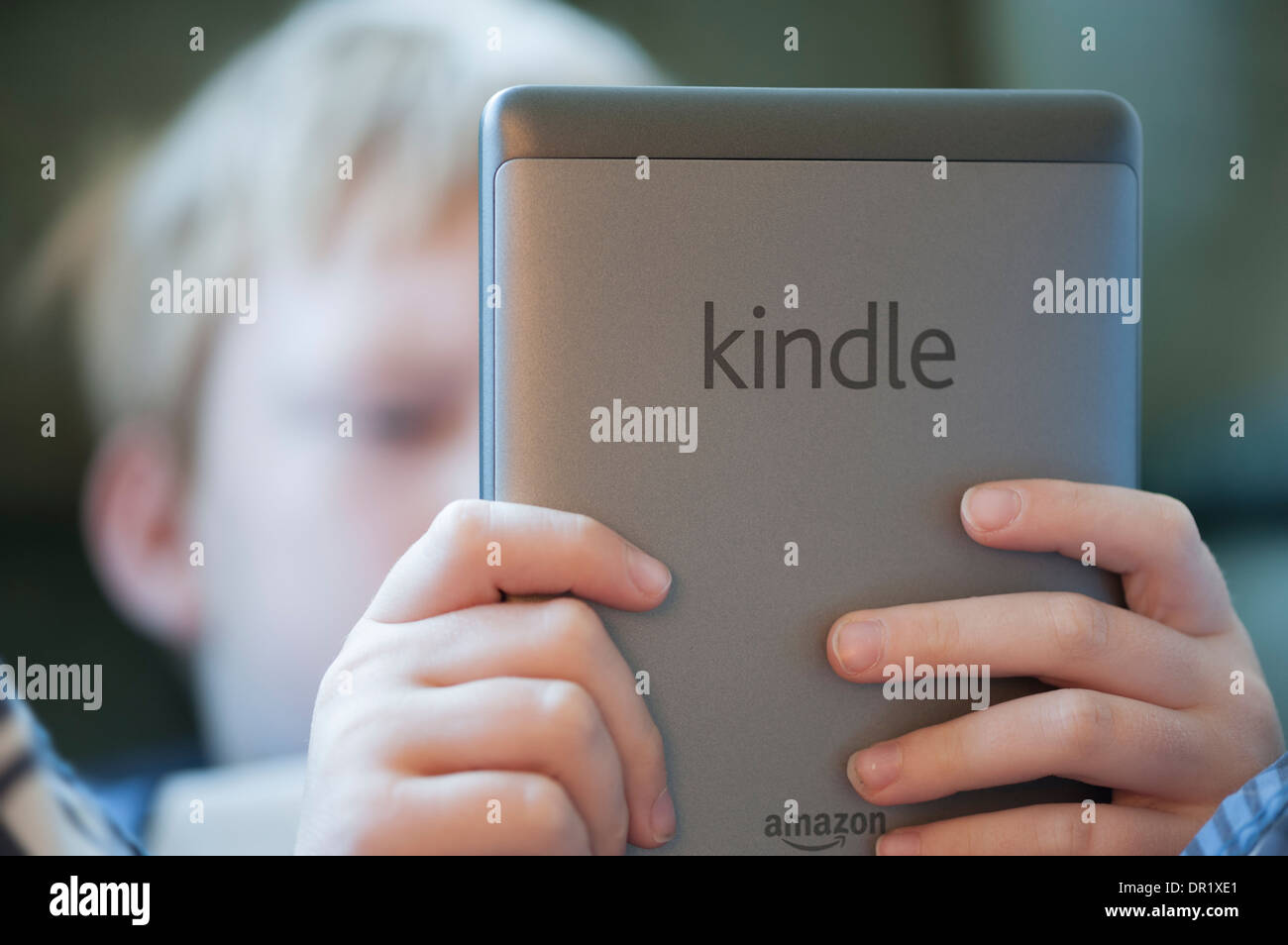 A 9-year old boy is reading an ebook on a Kindle ebook-reader - Stock Image