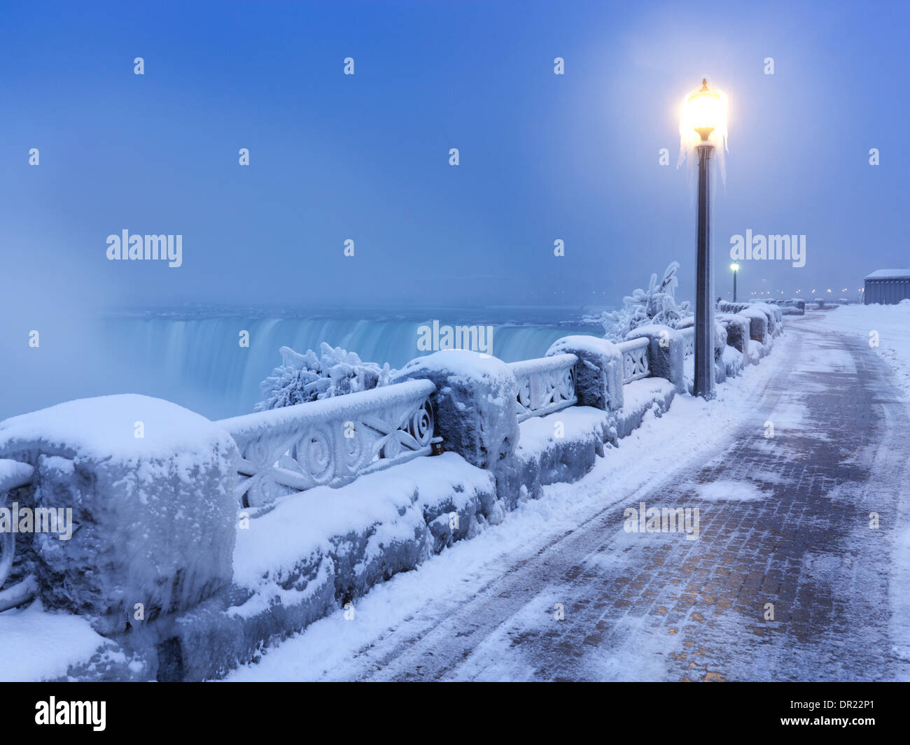 Sidewalk covered with snow and a lamp post, tranquil city scenery at Niagara Falls. Horseshoe waterfall wintertime - Stock Image