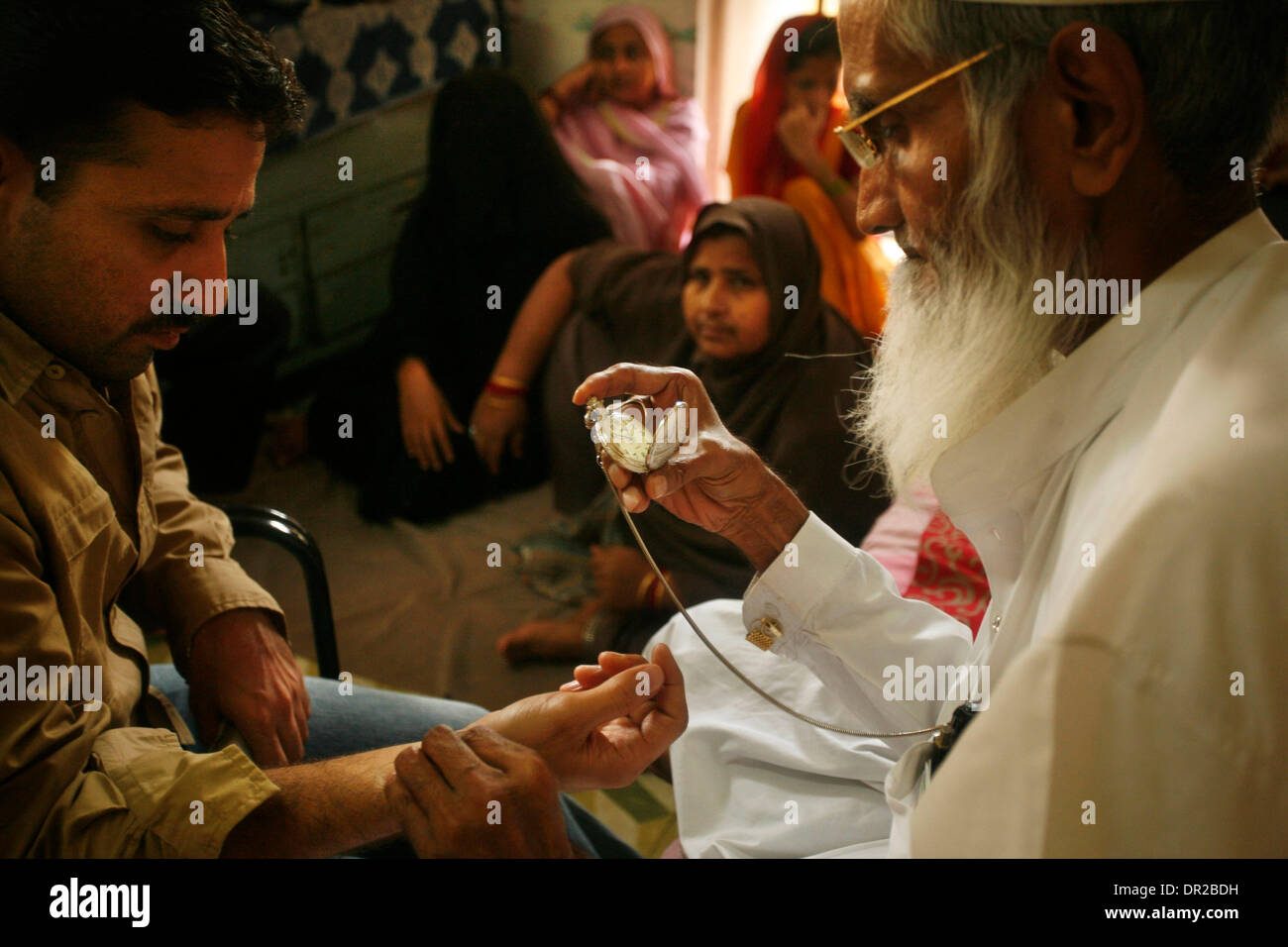 Jan. 12, 2009 - Amhedabad, India - A hakim takes the pulse of a man at his home in Ahmedabad, India.  A hakim is Stock Photo