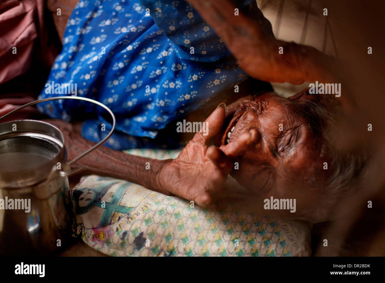 Jan. 12, 2009 - Amhedabad, India - An elderly blind woman suffering from polio lays under a cart on the side of Stock Photo