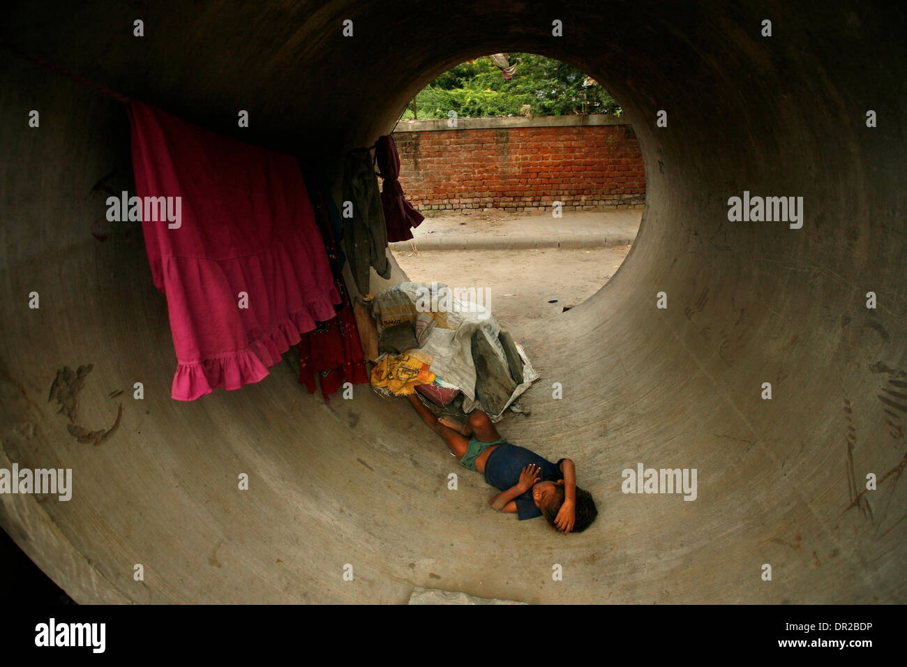 Jan. 12, 2009 - Amhedabad, India - A young boy sleeps in a concrete pipes on the side of the road in Amhedabad. Stock Photo