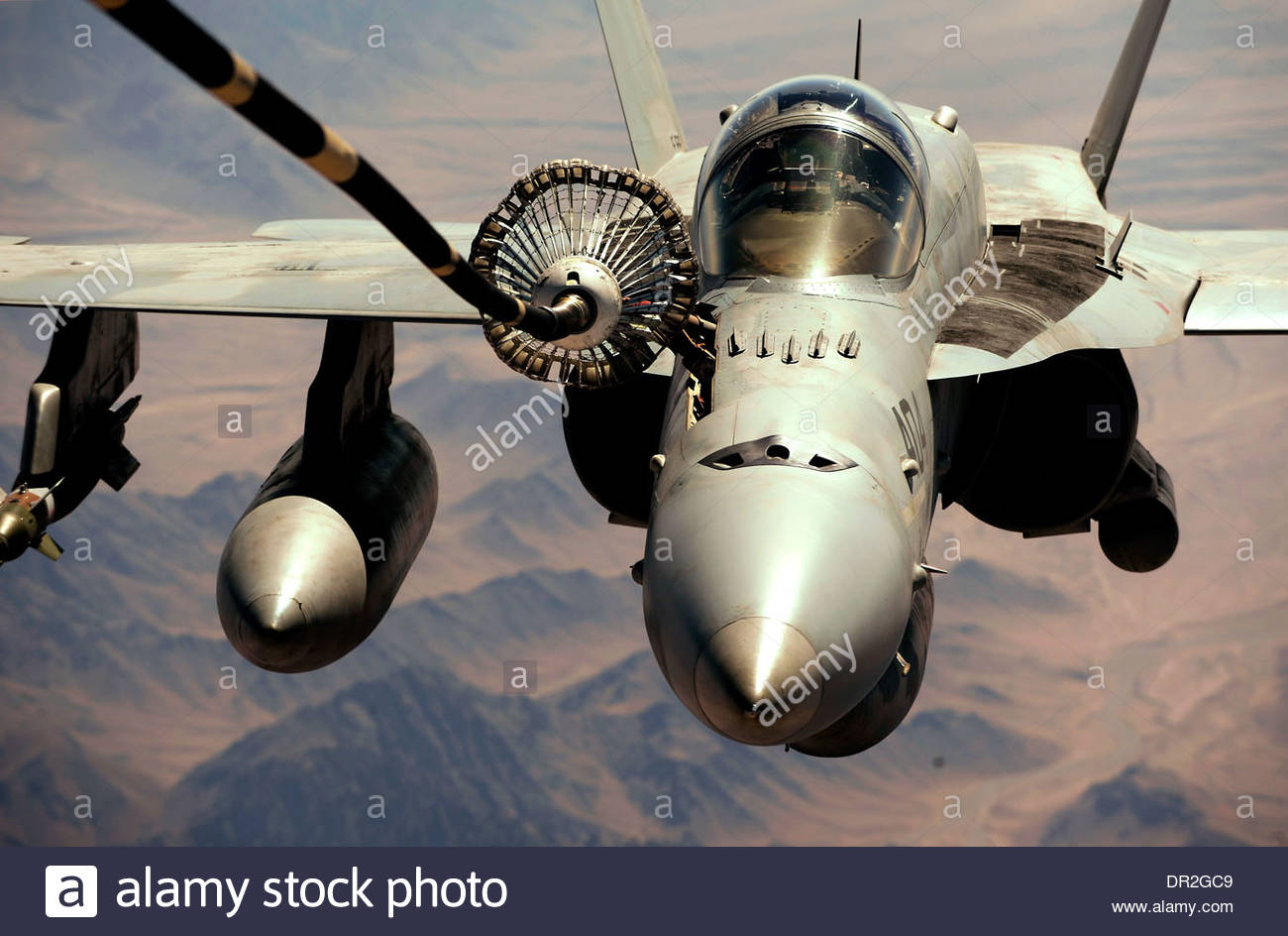 F/A 18C strike fighter receives fuel from the aerial refueling drone Stock Photo