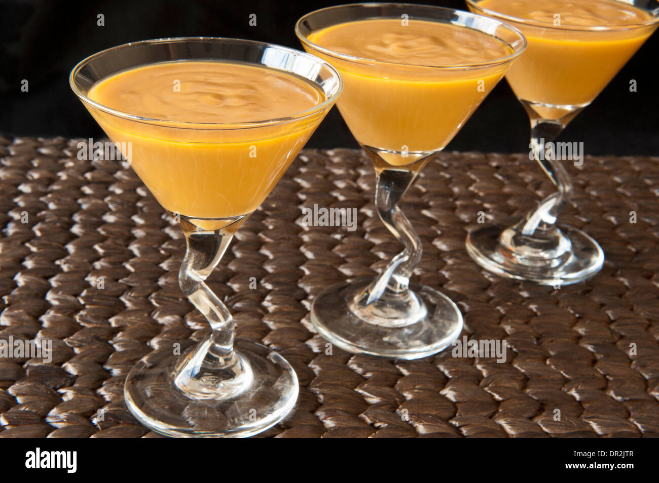 Butterscotch pudding in a martini glass on a woven mat Stock Photo