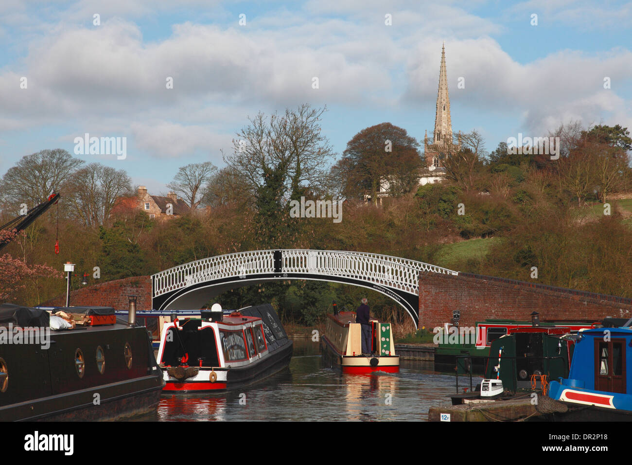 A narrowboat leaving Braunston marina on the Grand Union Canal and the spire of All Saints' Church, Braunston, Northants Stock Photo