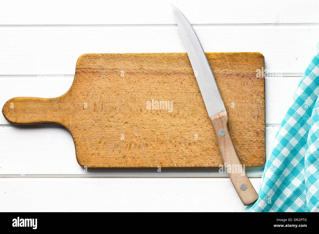 top view of cutting board with knife on white wooden table - Stock Image