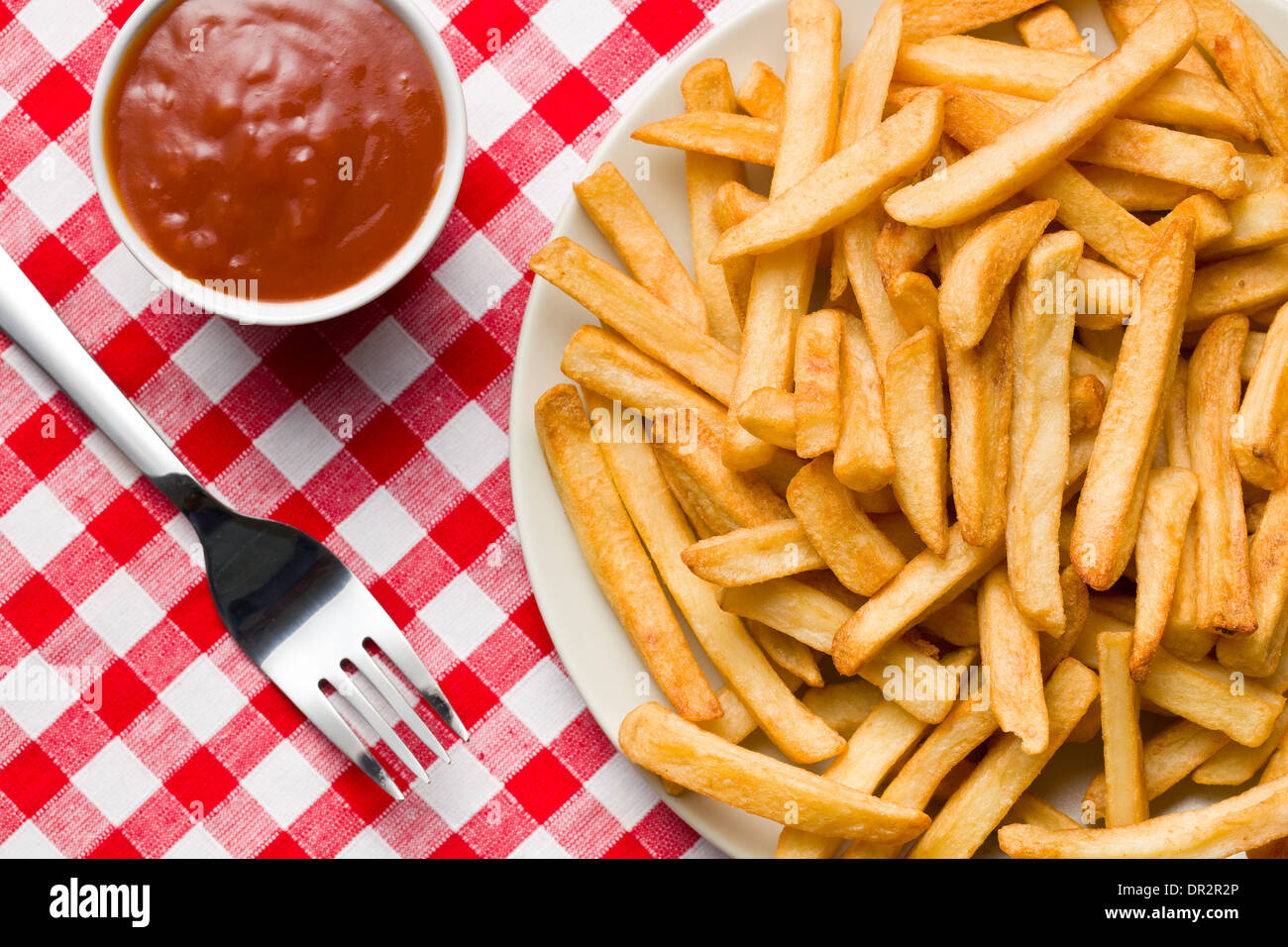 top view of french fries on plate with ketchup on checkered tablecloth - Stock Image