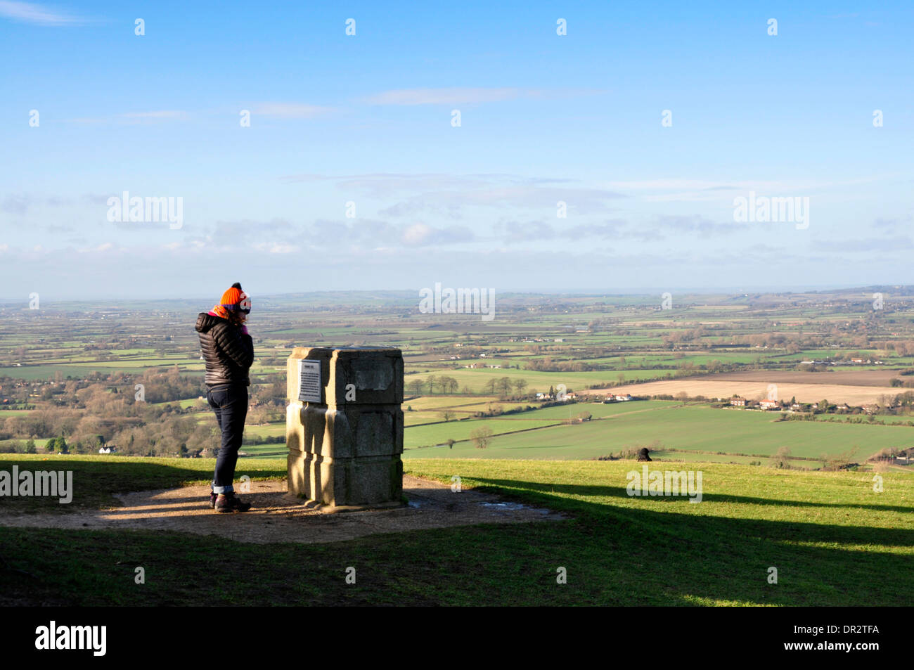 Bucks - Chiltern Hills - on Coombe Hill overlooking Vale of Aylesbury - walker pausing to read dedication stone - winter sun - Stock Image