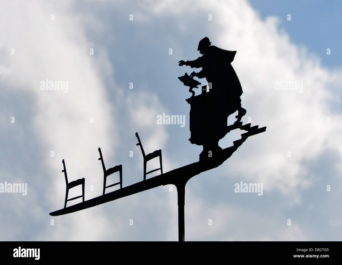 Unusual weather vane - preacher speaking to empty pews  - silhouette against the sky - white clouds and blue sky Stock Photo