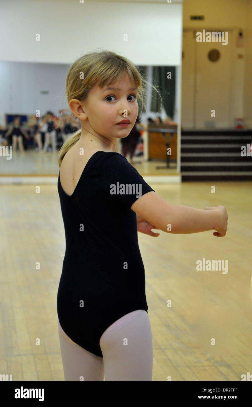 portrait of little blonde girl doing a ballet pirouette in a dancing class - Stock Image