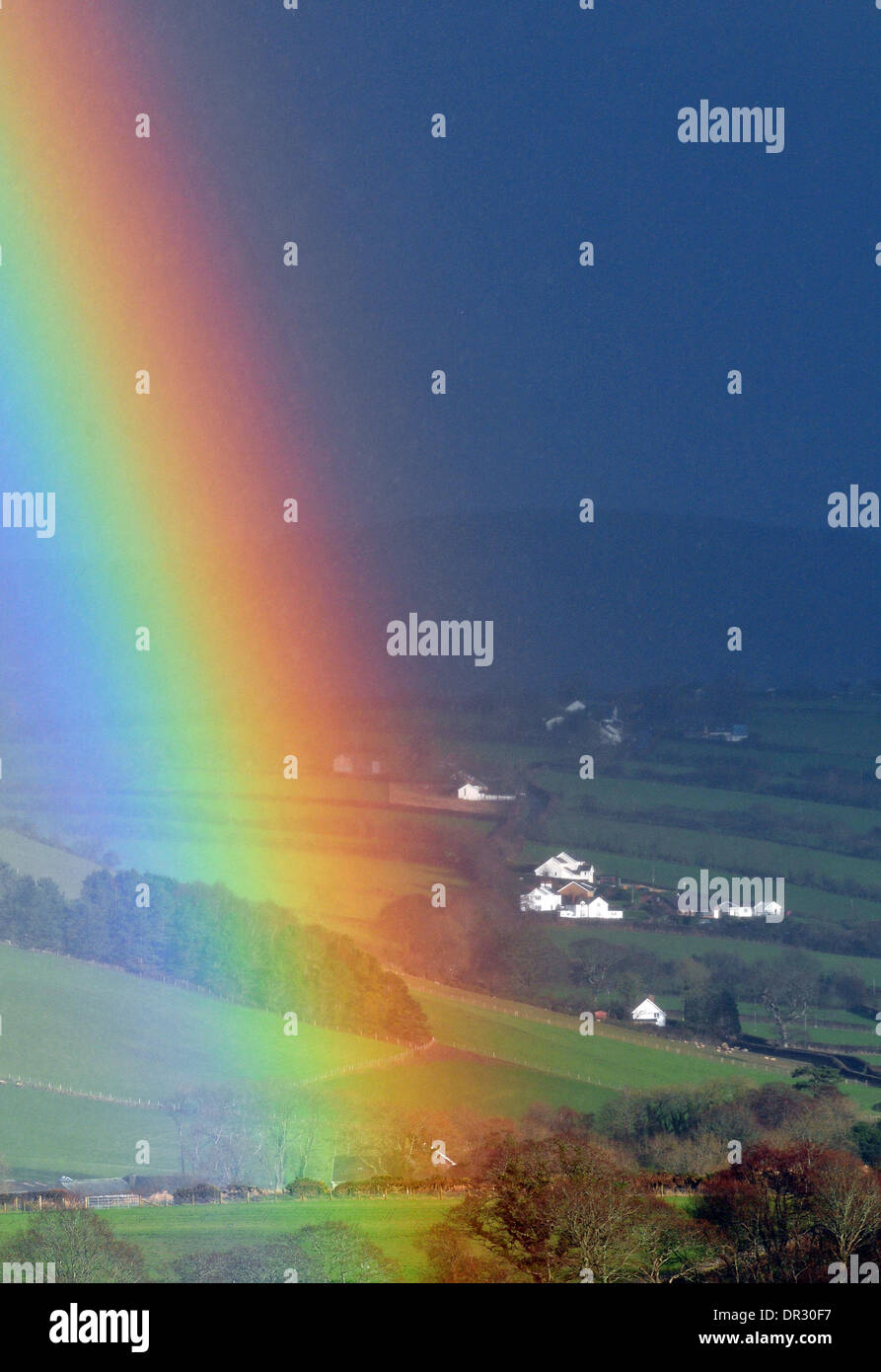Aberystwyth, Wales, UK. 18th Jan, 2014.  For the second time in two days, a rainbow crosses the view of the Cambrian Mountains behind Capel Dewi, Aberystwyth, Wales, UK as showers sweep across the valley - 18 Jan 2014. Credit:  John Gilbey/Alamy Live News - Stock Image