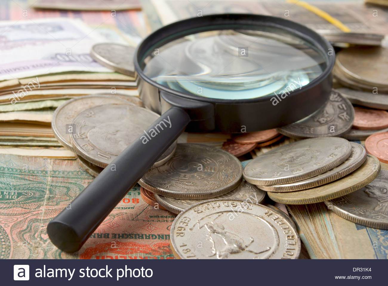 Still life of magnifying glass, coins and banknotes. - Stock Image