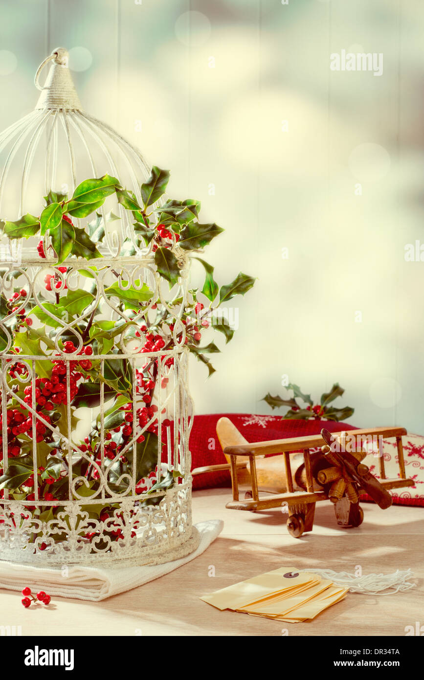 Birdcage filled with holly and berries with toy plane and tags with vintage filter effect - Stock Image