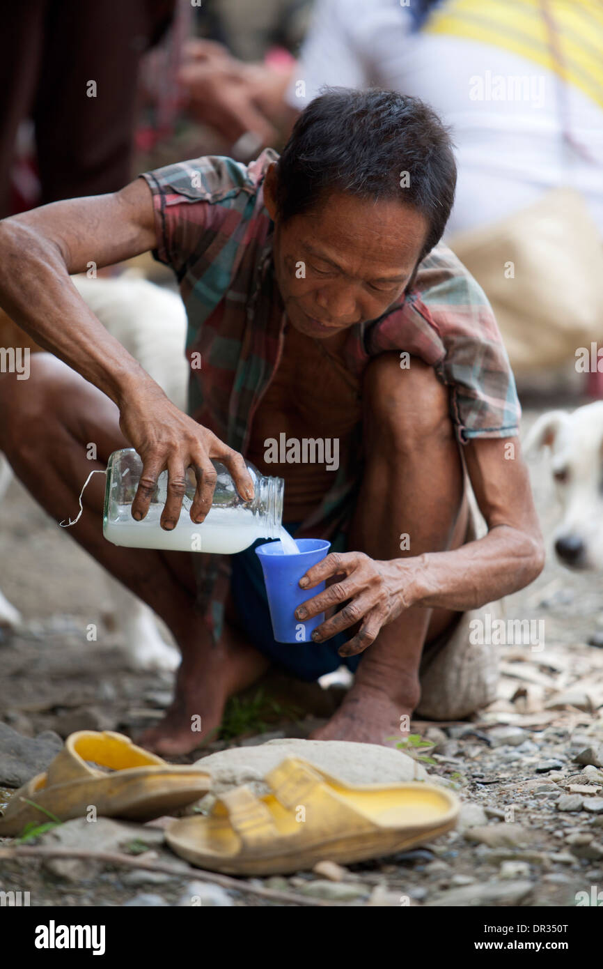 A Hanunoo Mangyan pours himself a cup of Tuba, coconut wine, at a Mangyan market near Mansalay, Oriental Mindoro, Philippines. - Stock Image