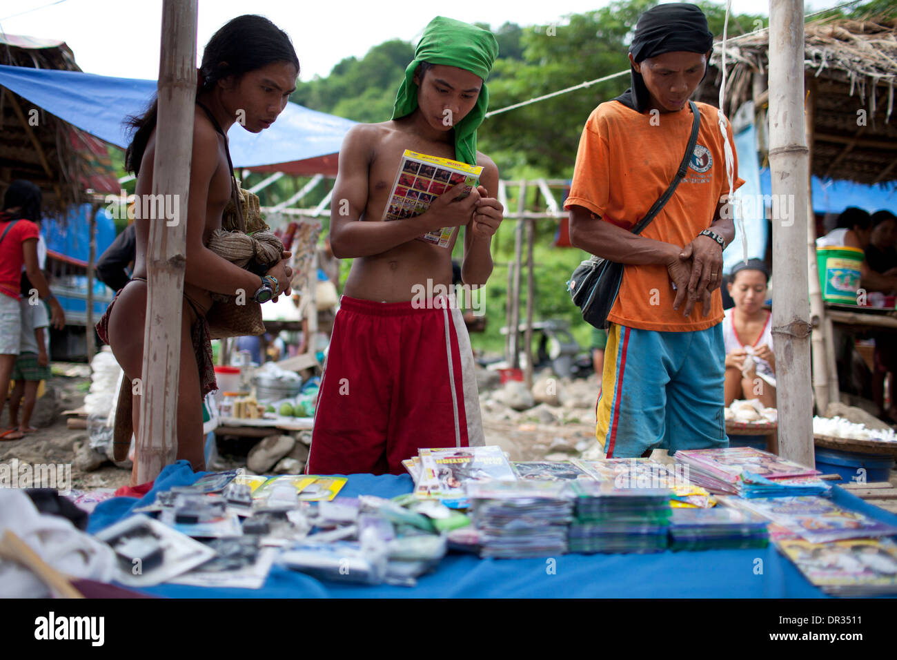 A Hanunoo Mangyans browse DVD titles for sale at a Mangyan market near Mansalay, Oriental Mindoro, Philippines. Stock Photo