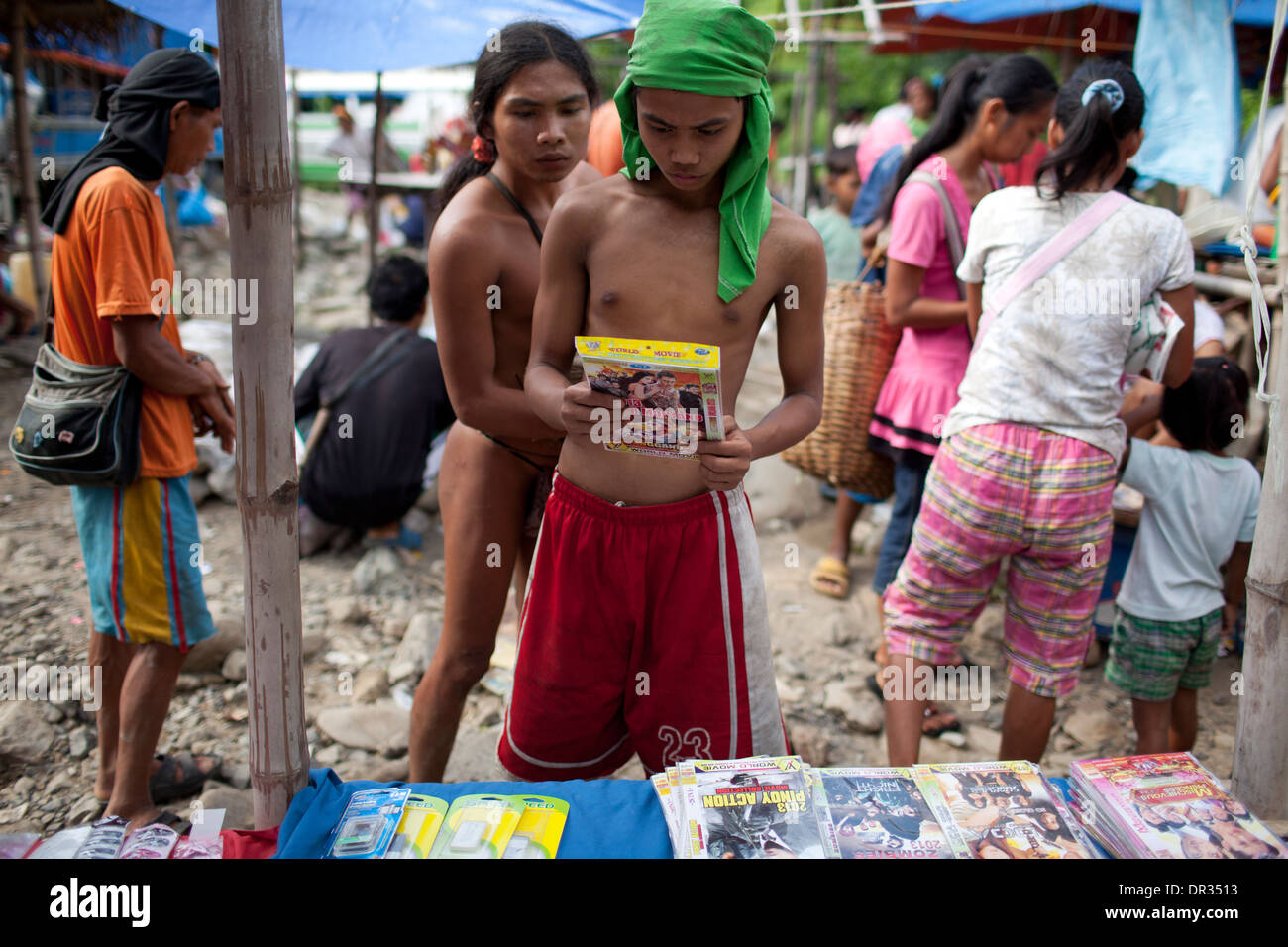 A Hanunoo Mangyan browses DVD titles for sale at a Mangyan market near Mansalay, Oriental Mindoro, Philippines. - Stock Image