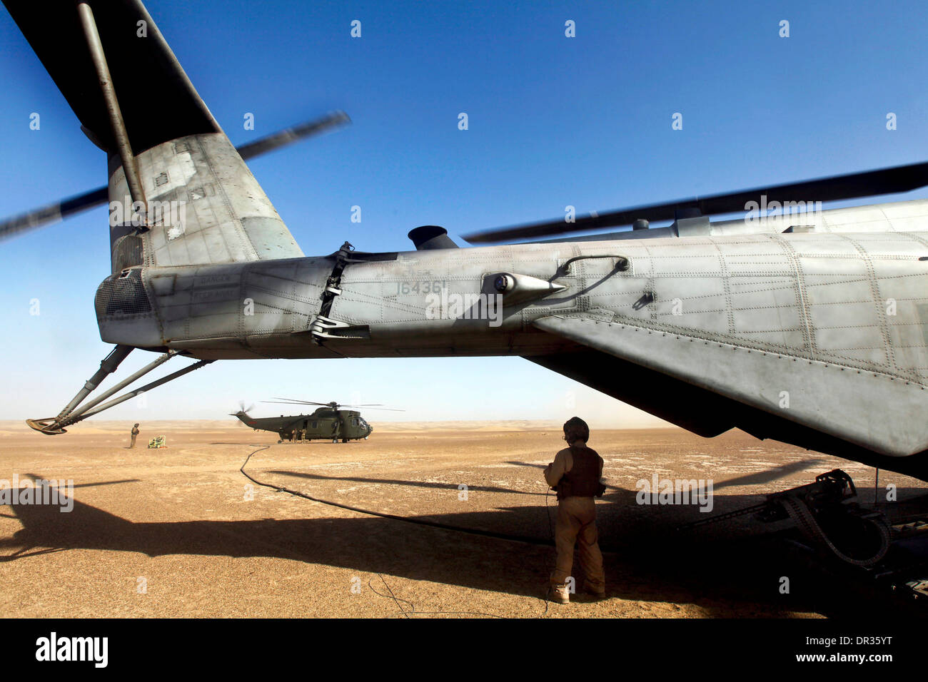 Crew chief with Marine Heavy Helicopter Squadron 462 watches as his Marines refuel a British Sea King MK4, Afghanistan Stock Photo