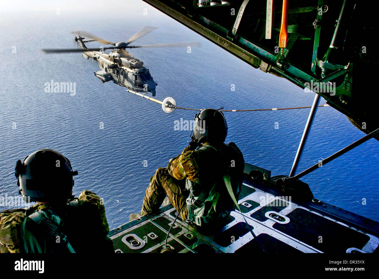 Loadmasters watch as a French air force Eurocopter practices aerial refueling - Stock Image
