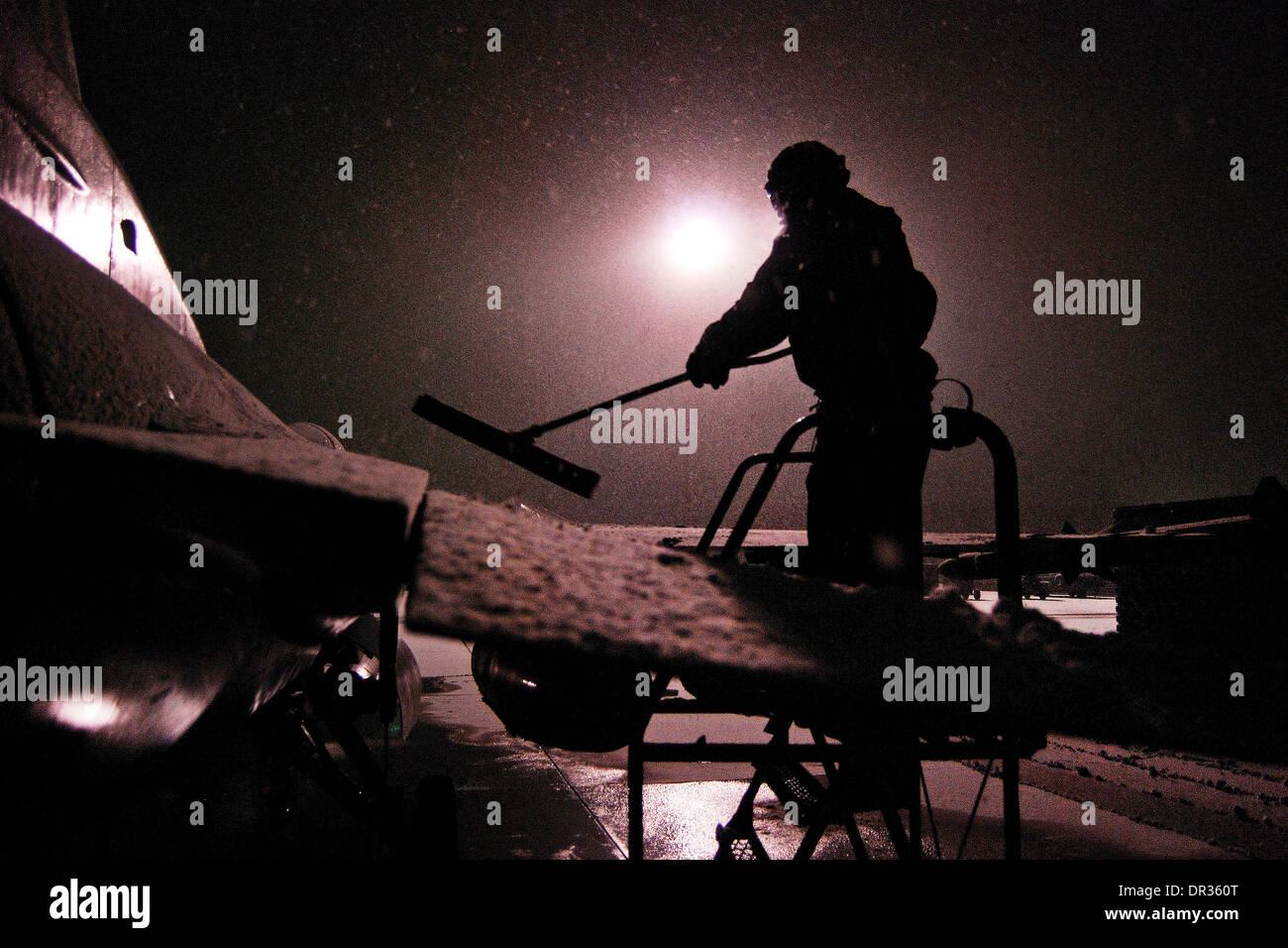 U.S. Airman clears snow off a F-16 Fighting Falcon, Afghanistan. - Stock Image