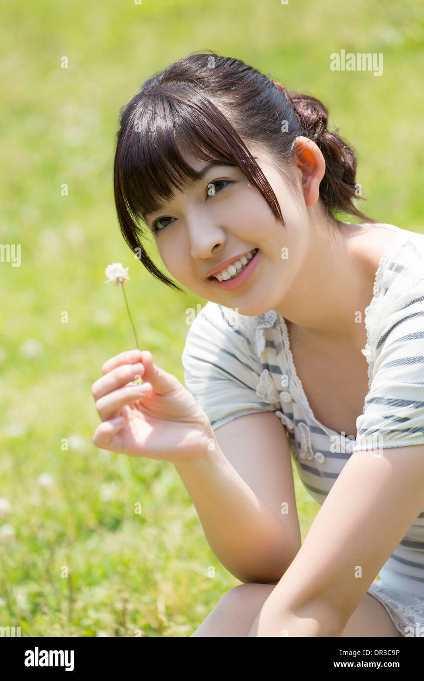 Young woman sitting on lawn - Stock Image