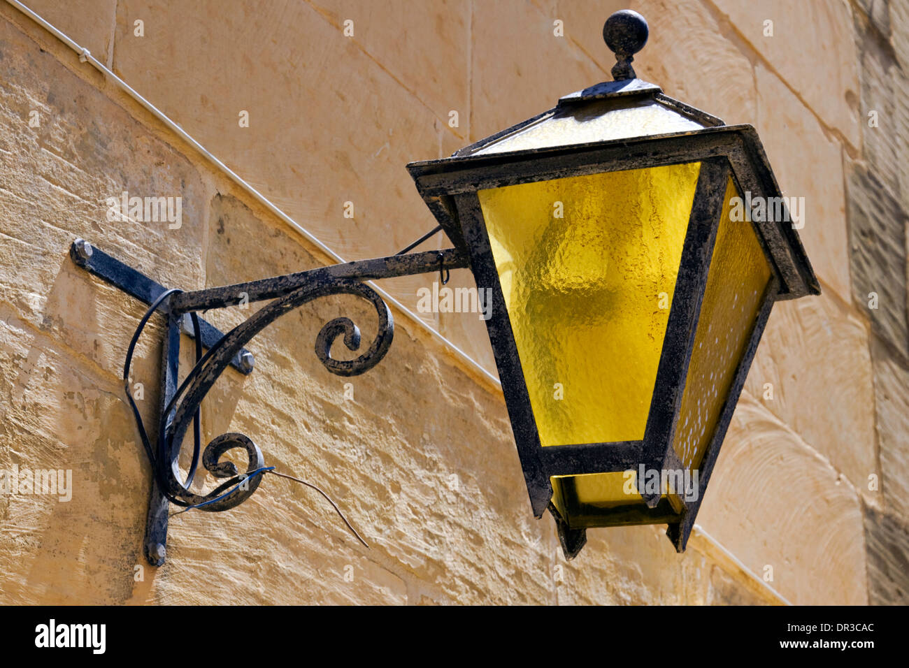 Wrought iron lamp with yellow glass on a limestone wall - Stock Image