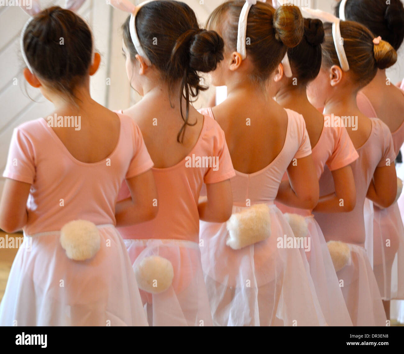 row of child ballerinas lined up with bunny tails - Stock Image
