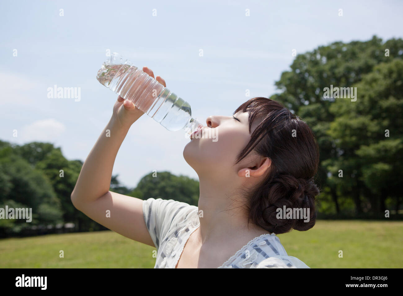 Young woman drinking water in a bottle - Stock Image