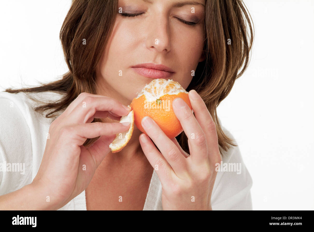 Woman sniffing an orange Stock Photo