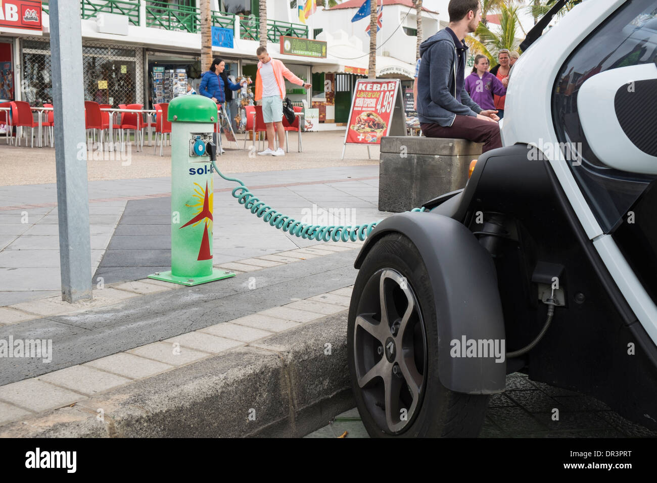 Renault Twizy battery-powered electric car plugged in to a Sol-lar battery charging point on roadside in Canary Stock Photo