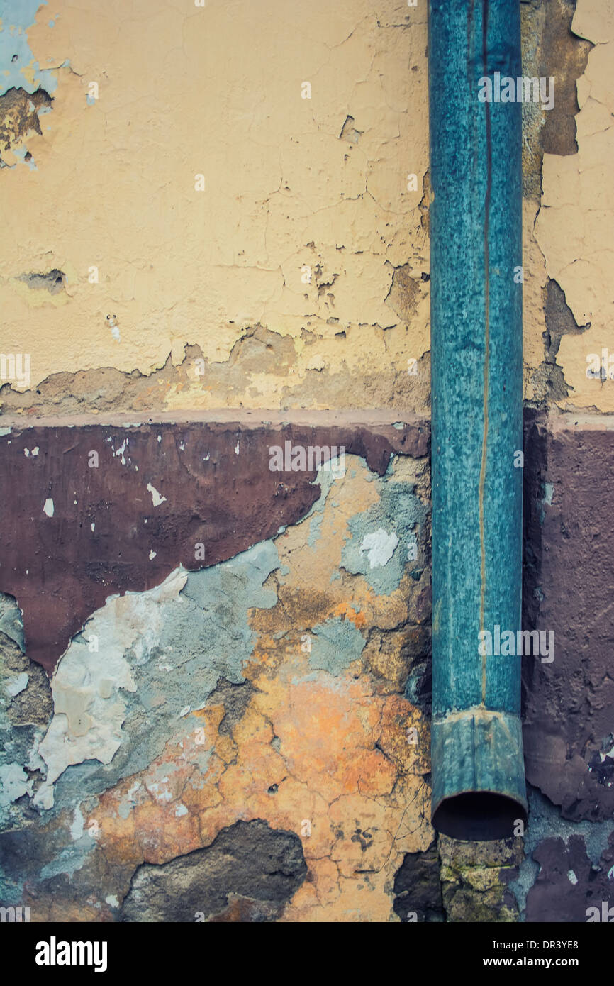 Old drainpipe on the chapped wall - Stock Image