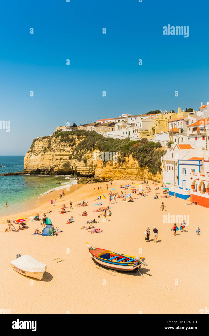 people on the beach, in the background houses built on the rock, carvoeiro, algarve, portugal Stock Photo