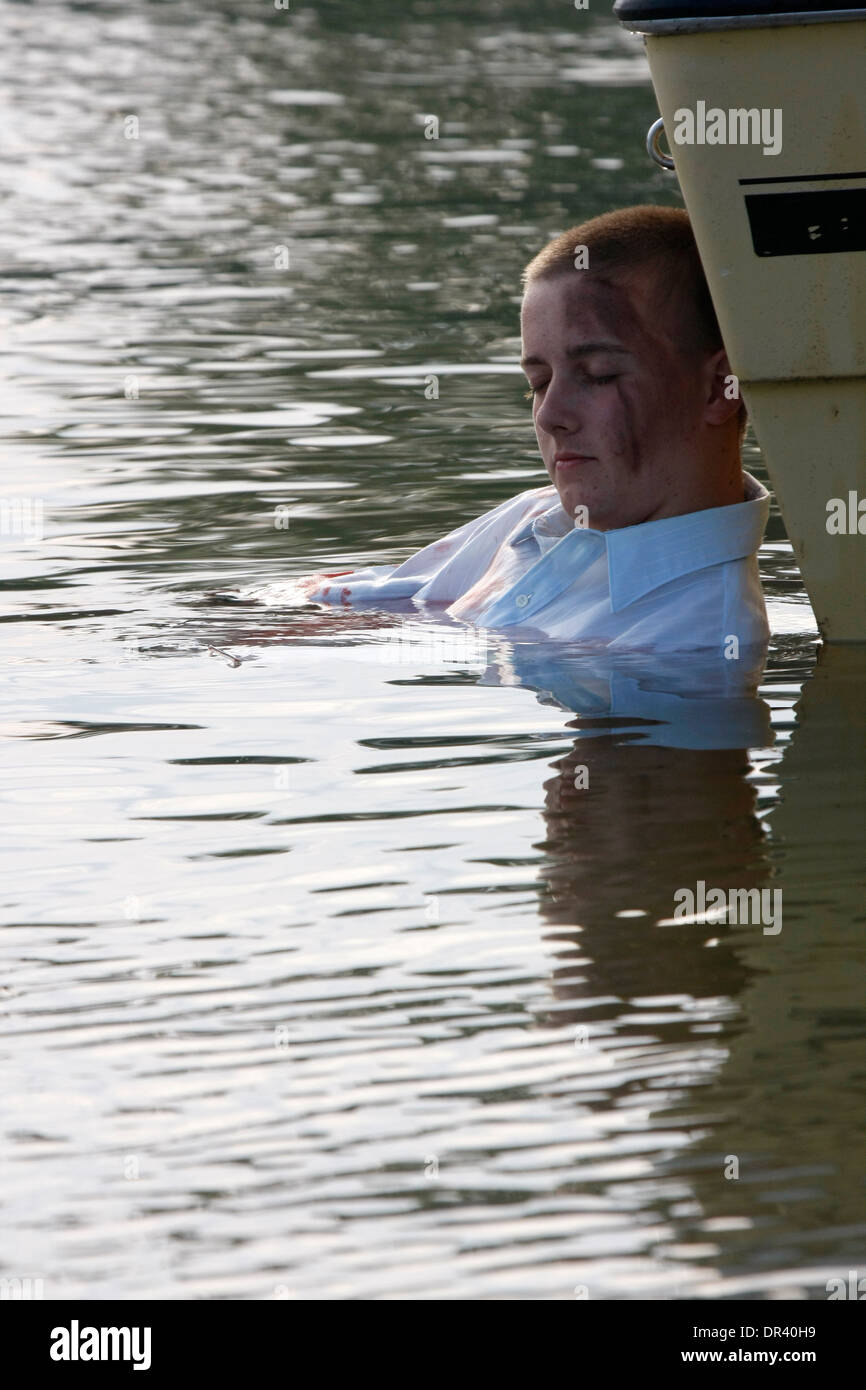 A boating accident victim in the water next to the boat - Stock Image