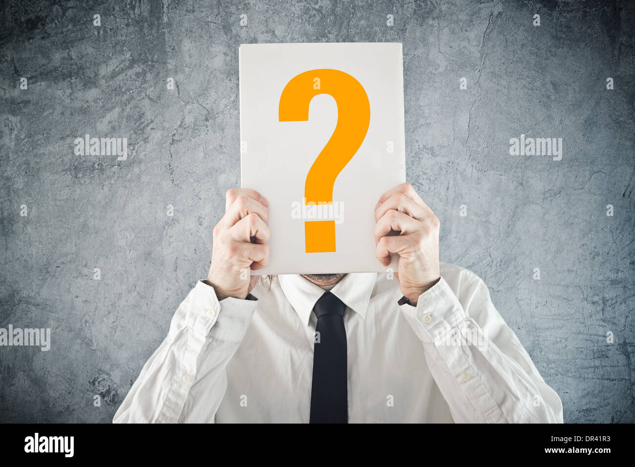 Businessman holding paper with printed question mark in front of his face - Stock Image