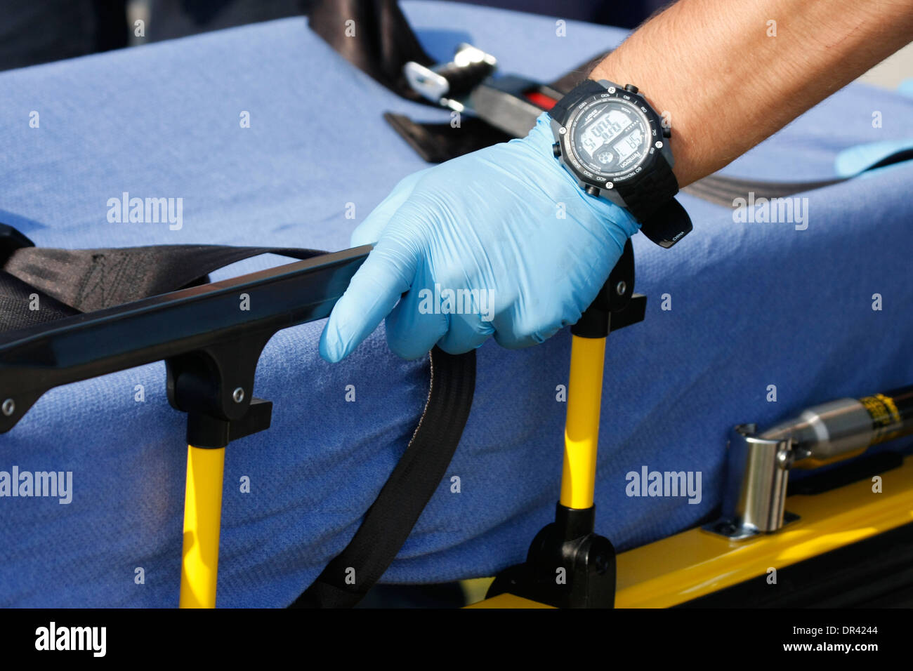 An EMT hand on a medical transport cot - Stock Image