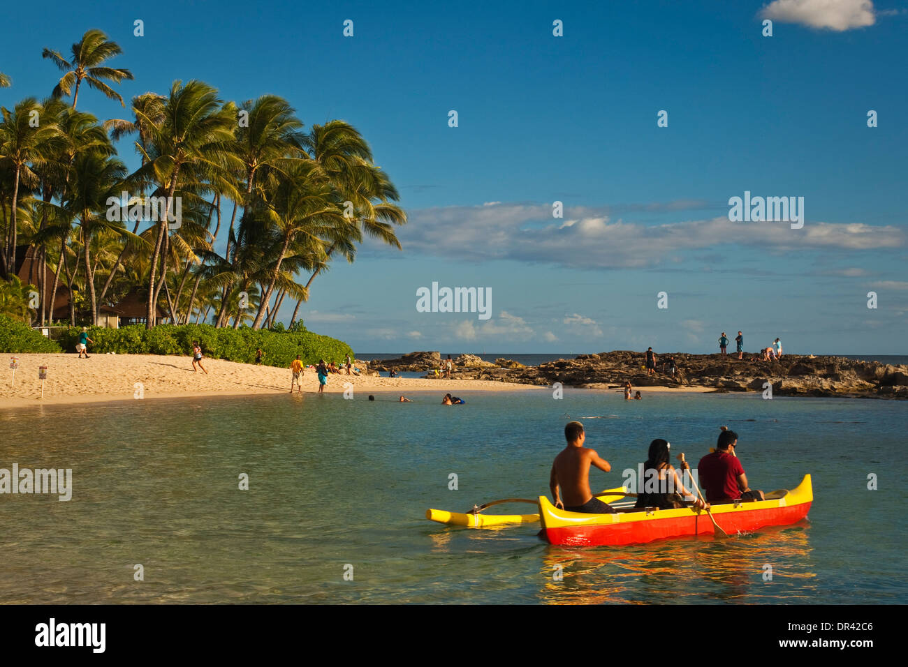 Tourists getting a ride in an outrigger canoe at the Paradise Cove Luau, Kapolei, Oahu, Hawaii - Stock Image