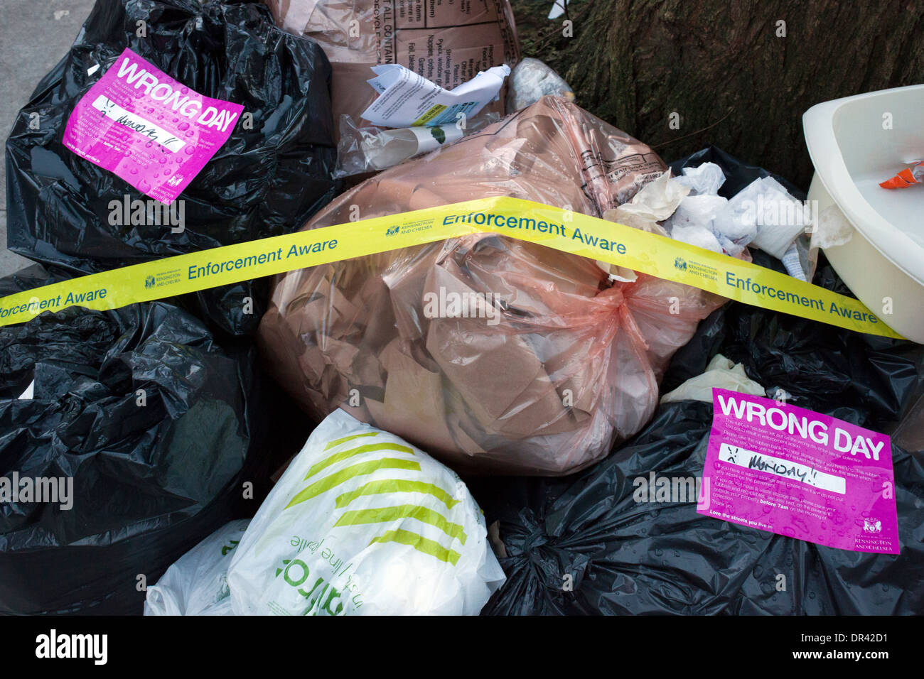 Household Waste in street with warning labels and tape - Stock Image