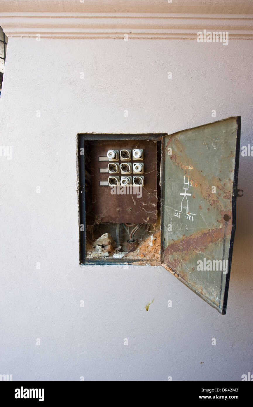 A wide-open fuse box in the wall in the street. - Stock Image