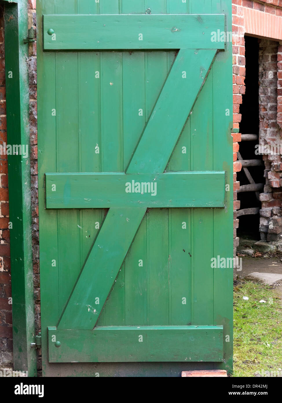 Green painted wooden door with letter 'Z' shaped battens - Stock Image