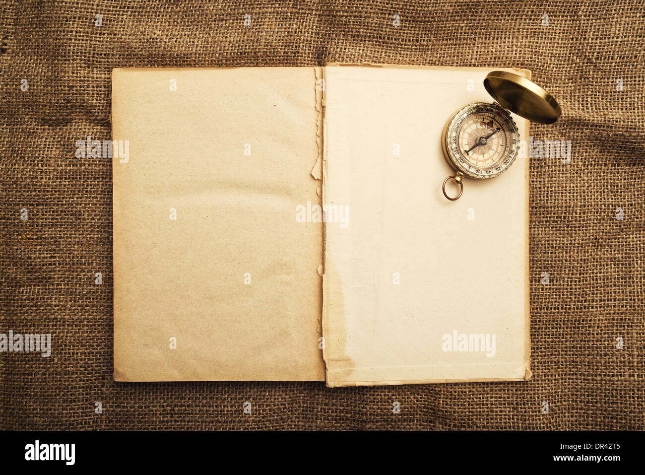 Vintage open book with old navigation compass. - Stock Image