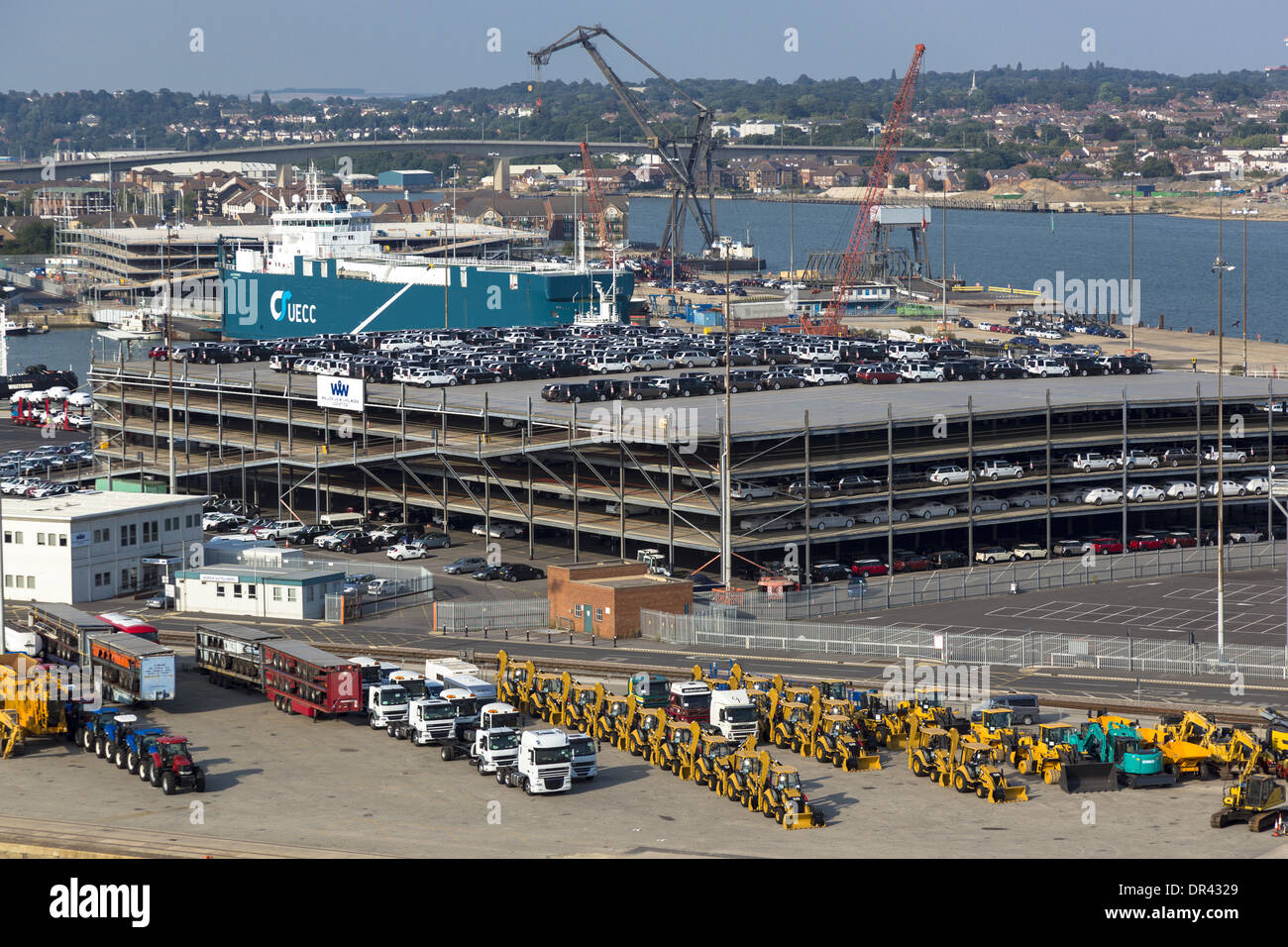 Cat tractors and cars lined up to be loaded on a ship at Southampton docks. M/V Autopride. The UK's principle automotive port. - Stock Image