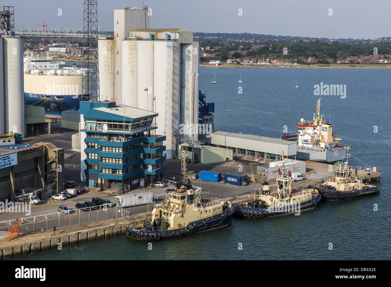 Tugs alongside dockhead, Southampton. Home to Port of Southampton Vessel Traffic Services in the blue building - Stock Image