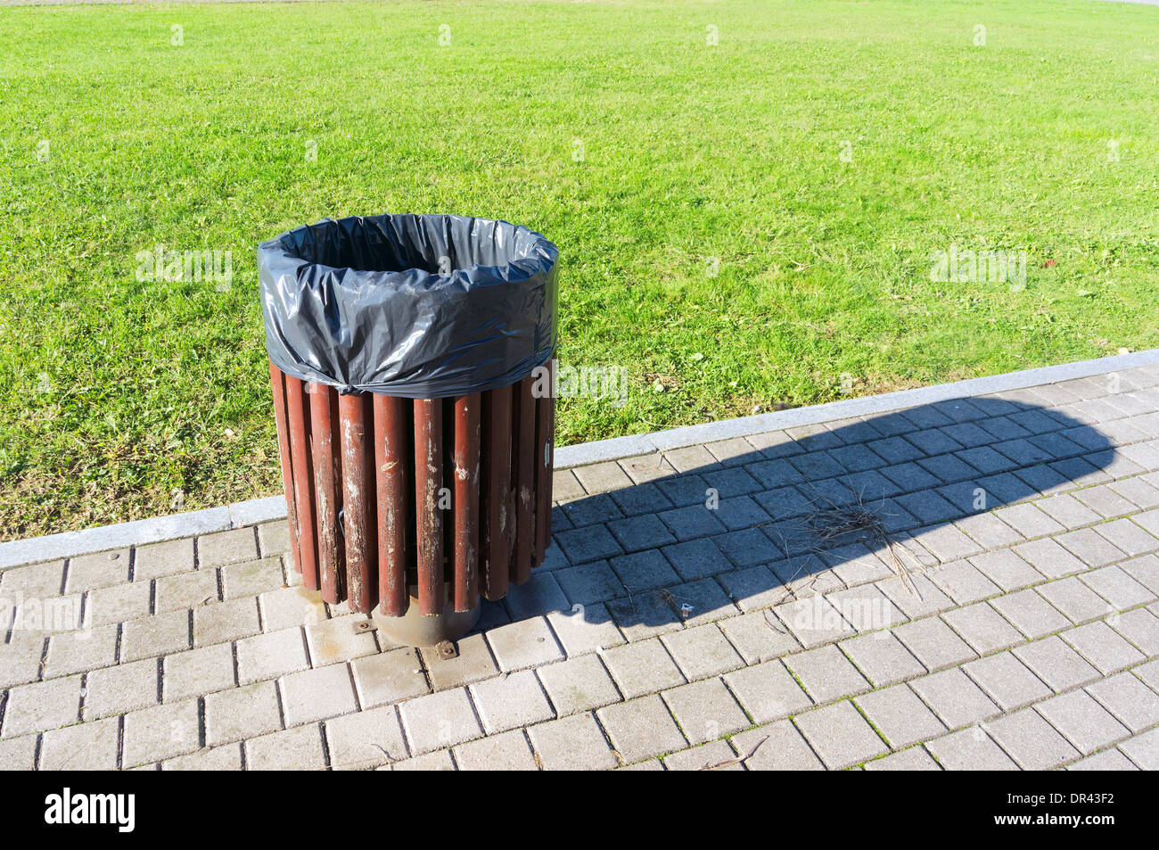 garbage can in a park - Stock Image