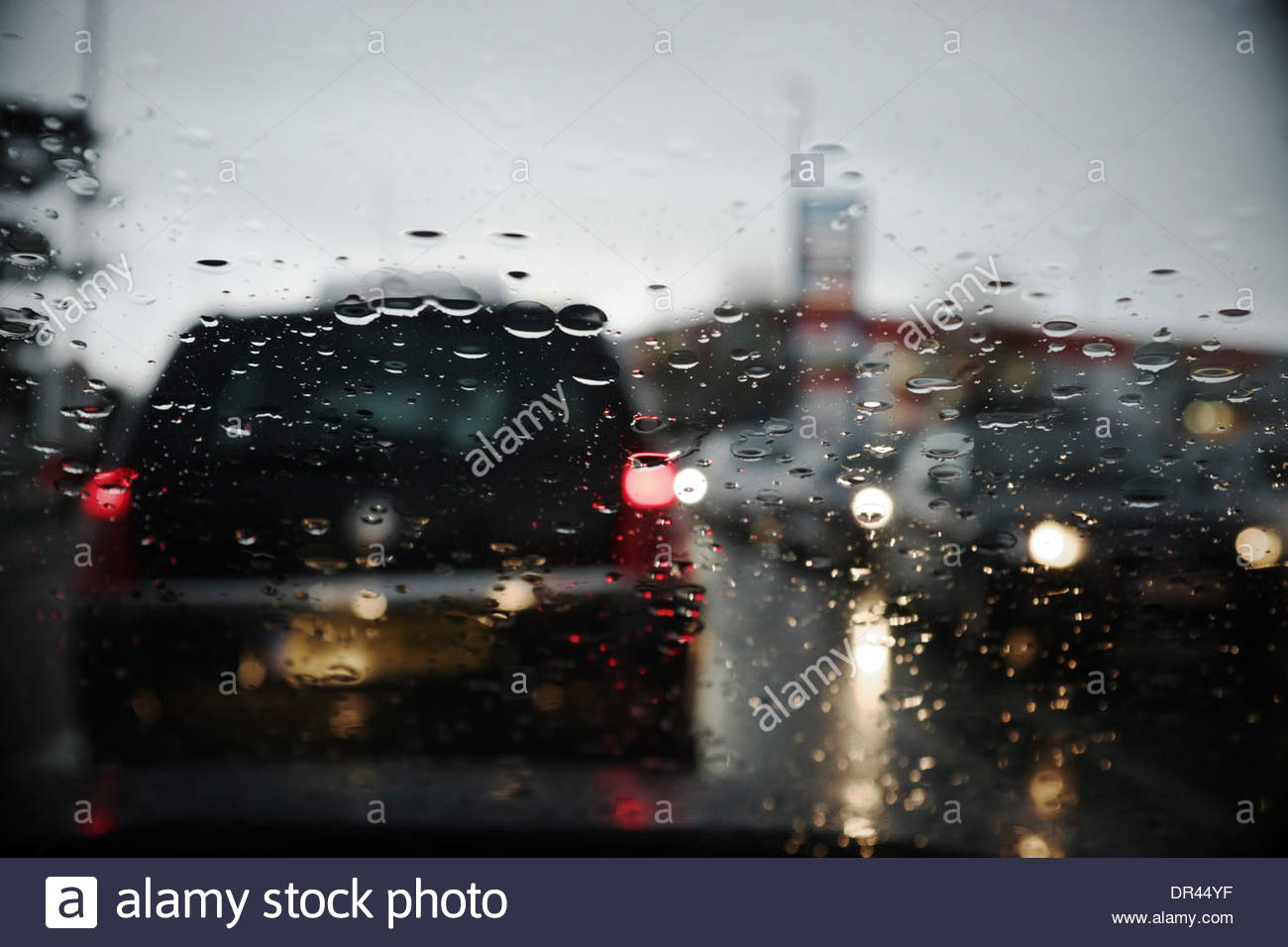 Rain droplets on the windscreen of a car stuck in a traffic jam. Bristol, UK. - Stock Image