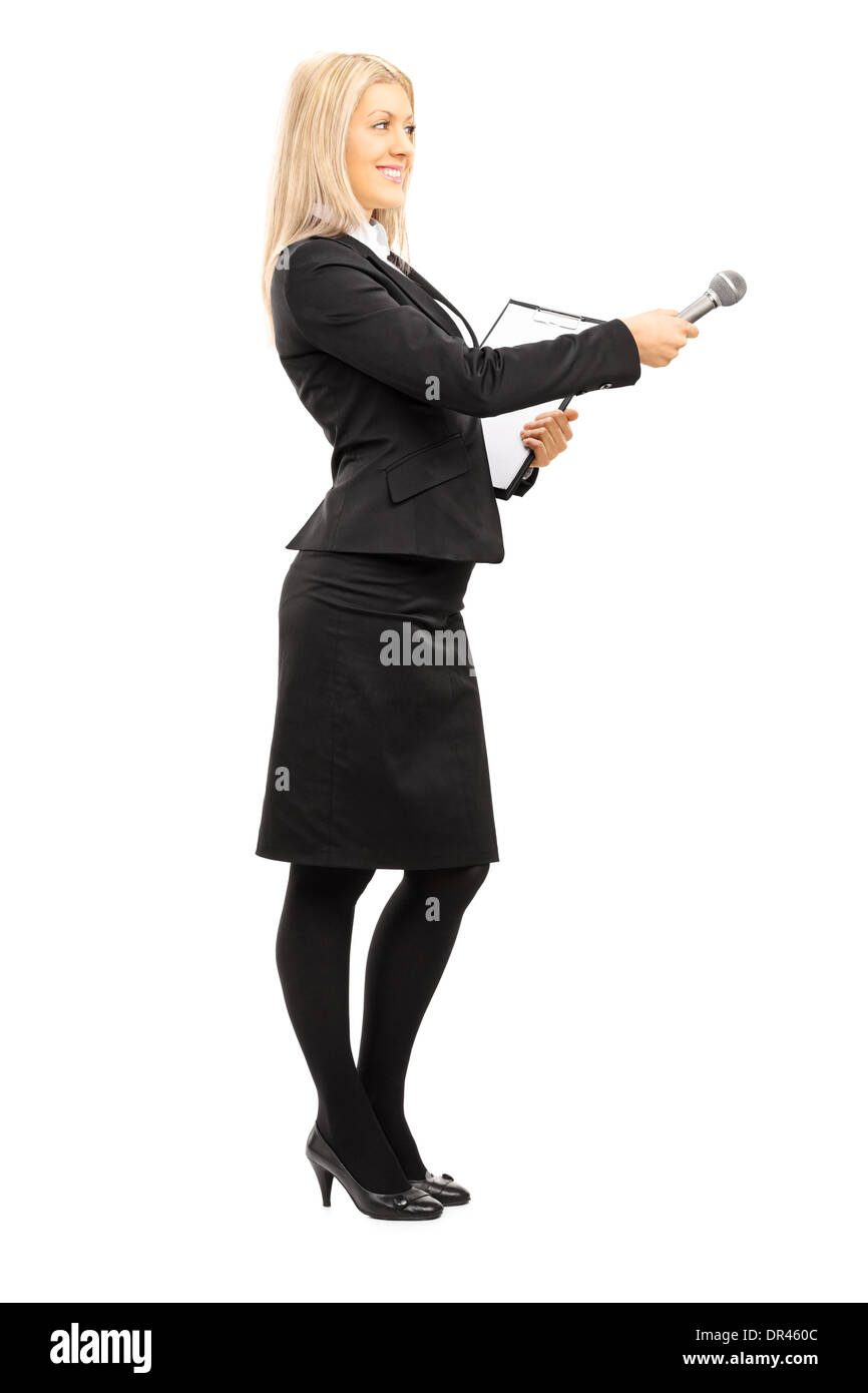 Full length portrait of young female interviewer holding a microphone - Stock Image