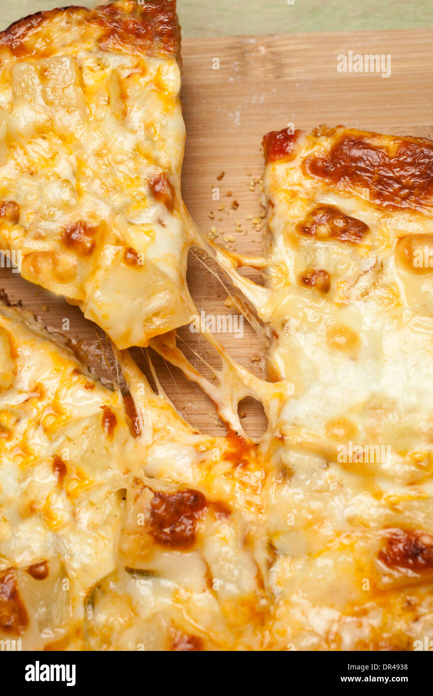 Grabbing the first slice of cheese pizza - Stock Image